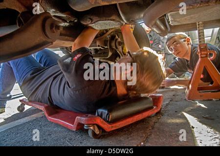 Sicherheit trägt Brille eine kaukasische Teenager Mädchen und jungen arbeiten unter einem Automotor im Auto-laden - Stockfoto