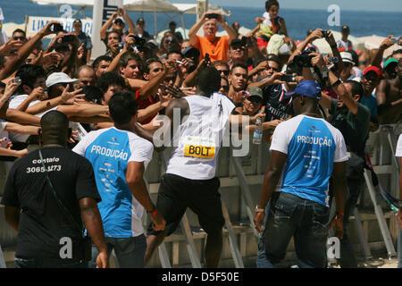 """Jamaikaner Usain Bolt begrüßt das Publikum nach dem Gewinn der 150m """"Mano a Mano""""-Herausforderung in Copacabana - Stockfoto"""