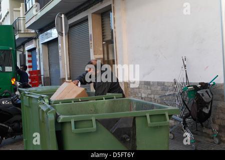 Ein arbeitsloser Mann zieht einen Wagen um den Müll auf den Lagerplätzen gefunden zu tragen. - Stockfoto