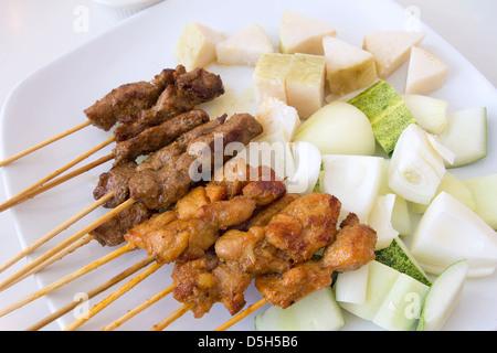 Hammel und Chicken Satay mit gehackten Gurken Zwiebeln und Ketupat Reis Kuchen - Stockfoto