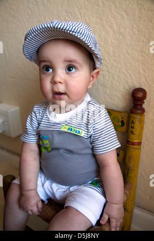 Baby Boy Portrait tragen Mütze und sitzen auf Stuhl - Stockfoto