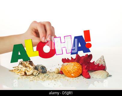 """Weiblichen Hand mit bunten Wort """"Aloha"""" vor weißem Hintergrund - Stockfoto"""