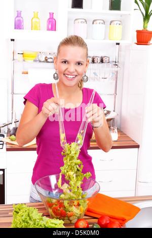 Lächelnde junge Mädchen machen einen frischen Salat in der Küche - Stockfoto