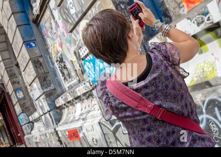 Eine junge Frau nutzt ihr Kamera-Handy zum Fotografieren von Graffiti auf einem Gebäude. - Stockfoto