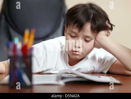 Schule junge Studien schwer über sein Buch zu Hause. - Stockfoto