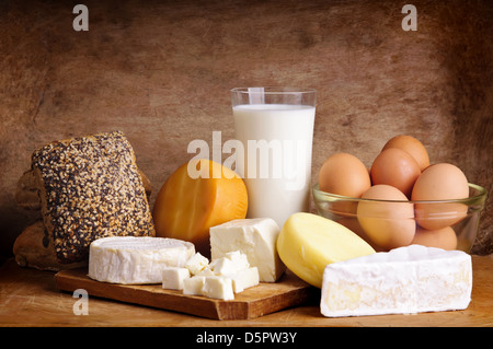 Stillleben mit Milchprodukten, Milch, Eiern, Brot und Käse auf einem Vintage Holz-Hintergrund - Stockfoto