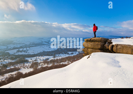 Wanderer im Schnee bedeckt Gipfel am Curbar Rand Peak District Nationalpark Derbyshire England GB UK EU Europa - Stockfoto