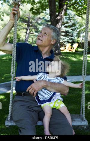 Großvater und Enkelin auf Schaukel - Stockfoto