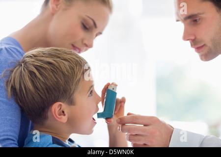 Eltern geben Sohn Asthma-Inhalator - Stockfoto