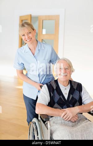 Pflegeperson älteren Mann im Rollstuhl schieben - Stockfoto