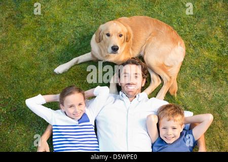 Familie mit Hund auf Wiese entspannen - Stockfoto