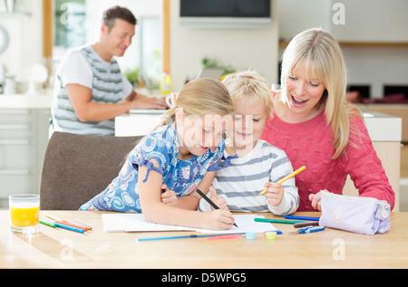 Mutter und Kinder Färbung am Tisch - Stockfoto