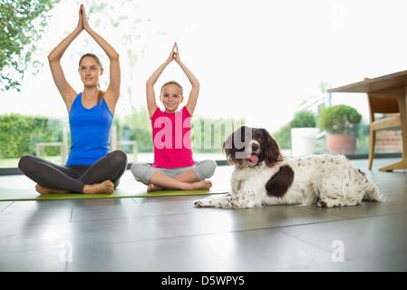 Hundesitting mit Mutter und Tochter Yoga zu praktizieren - Stockfoto