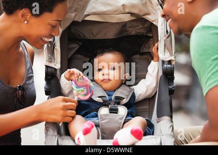 Eltern im Gespräch mit Baby im Kinderwagen auf Stadt Straße - Stockfoto