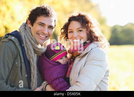 Familie lächelnd zusammen im park - Stockfoto