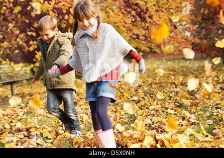 Kinder spielen im Herbstlaub - Stockfoto