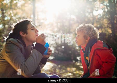 Vater und Sohn Seifenblasen im park - Stockfoto