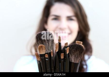 Glückliche junge Frau zeigt eine Vielzahl von Make-up Pinsel - Stockfoto