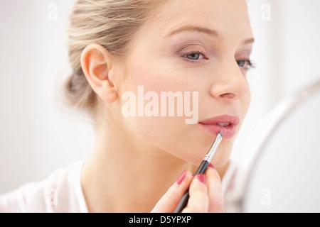 Frau Auftragen von Lippenstift mit Make-up Pinsel
