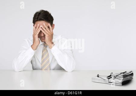 Besorgt Geschäftsmann t Tisch mit Bündel Geldscheine in Mausefalle aus finanziellen Schwierigkeiten - Stockfoto