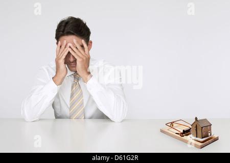 Besorgt Geschäftsmann t Tischmodell zu Hause in Mausefalle für teure Immobilienkosten - Stockfoto
