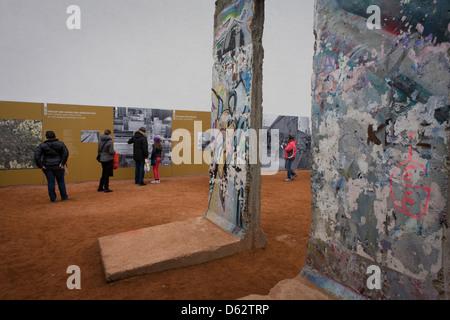 Besucher lesen Sie unter alten Abschnitte der Berliner Mauer Freigelände Platten in der Nähe der ehemaligen Checkpoint - Stockfoto