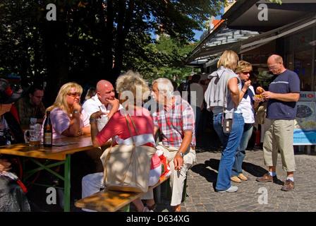 München, Bayern, Deutschland. Leute Essen, trinken und entspannen in der Viktualienmarkt südlich vom Stadtzentrum - Stockfoto