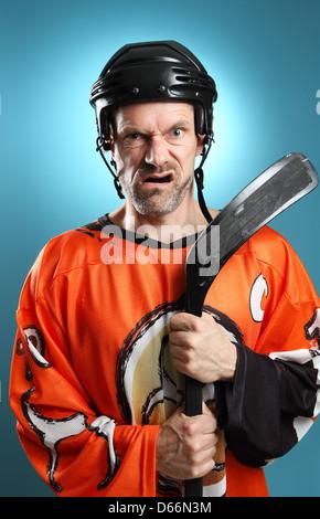 Humorvolle Schuss ein Eishockey-Spieler stützte sich auf seinen Hockeyschläger Ausdruck wütenden machen. - Stockfoto
