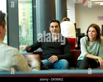 Geschäftsleute, die im Büro Lobby entspannen - Stockfoto
