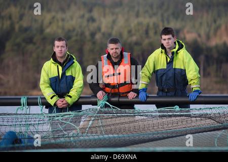 Arbeitnehmer auf Lachsfarm im ländlichen See - Stockfoto