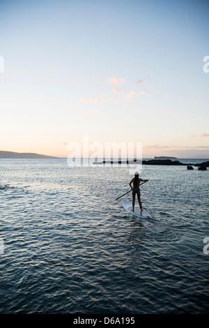 Frau Paddling am Ozean - Stockfoto