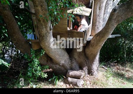 Kleine Mädchen spielen in einem Baumhaus während der Sommersaison. - Stockfoto