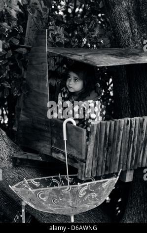 Kleines Mädchen bekommen während der Regen Unterschlupf in einem Baumhaus. - Stockfoto