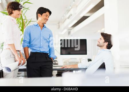 Business-Leute an der Rezeption sprechen - Stockfoto