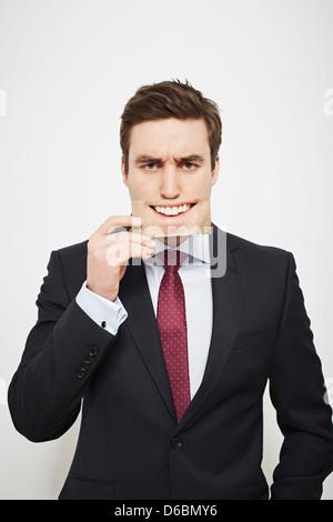 Geschäftsmann hält böse Bild über sein Gesicht - Stockfoto