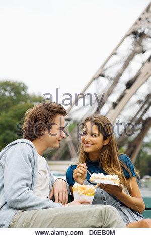Junges Paar Fastfood mit Eiffel Turm im Hintergrund Paris Frankreich - Stockfoto