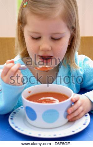Kleine Mädchen essen eine Schale mit Sahne Tomatensuppe - Stockfoto