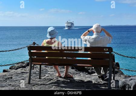 Ein älteres Ehepaar sitzen auf einer Bank in Playa Blanca, Lanzarote, beobachtet die Ankunft der Armas-Fähre Volcan - Stockfoto