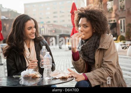 Frauen essen gemeinsam im Straßencafé - Stockfoto