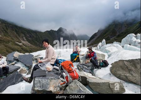 Touristen Essen ein Picknick auf dem Fox-Gletscher. Südinsel, Neuseeland - Stockfoto