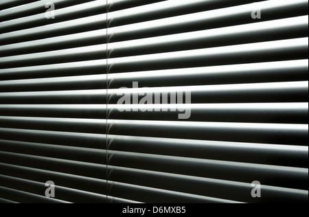 Tageslicht, das durch geschlossenen metallischen Jalousien, kontrastreiche abstrakte Muster. - Stockfoto