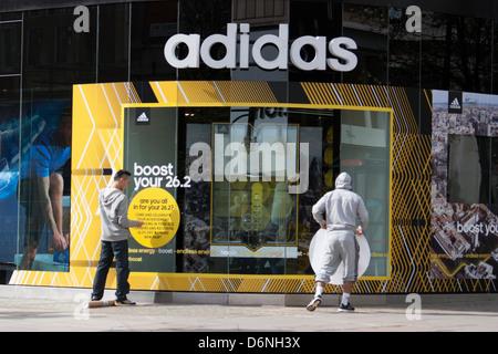 Adidas store Oxford Street London, Shop Arbeiter Pasten Logo außerhalb Shops - Stockfoto