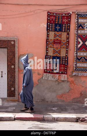 Berber Mann zu Fuß durch Marokko, mit hängenden Teppiche - Stockfoto