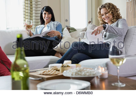 Glücklich Freundinnen mit Weingläsern und Bücher auf Hausparty - Stockfoto