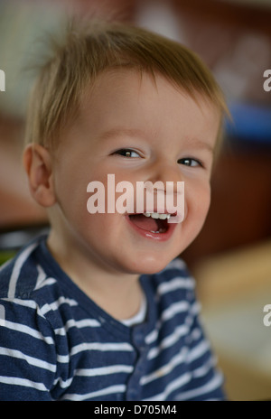Ein Foto von lächelnden Kleinkind im Alter von achtzehn Monate alt, mit braunen Haaren tragen eine blaue und weiße - Stockfoto