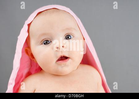 Porträt eines Mädchens überrascht neugeborenes Baby mit rosa Decke auf den Kopf - Stockfoto