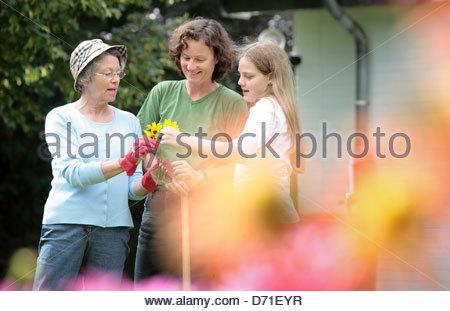 Familienholding Blumen in einem Garten - Stockfoto