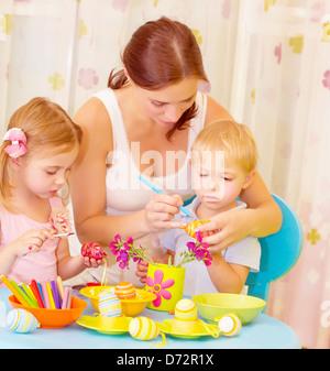 Zwei kleine süße Kinder mit schönen Mutter malen Ostereier zu Hause, Mama Lehre Babys schmücken Osterzeit symbol - Stockfoto