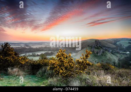 Eine frostige April Sonnenaufgang mit Blick auf die Ruinen von Corfe Castle auf der Isle of Purpeck in Dorset - Stockfoto