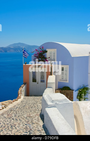 Schönes Haus mit Griechenland Flagge auf der Straße in Santorini Oia. Ägäische Meer im Hintergrund, Griechenland - Stockfoto